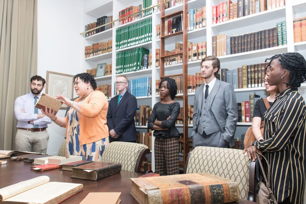 Library Director Miriam Child presenting rare law books to LLM students